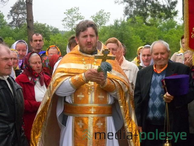 Священник читает молитву, окропляя храм и прихожан святой водой