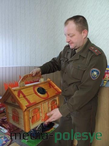 В руках Олега Володкевича поделка Ксении Реутской из Теребежовской СШ «Возьмёмся за руки, друзья, спасём наш мир мы от огня»
