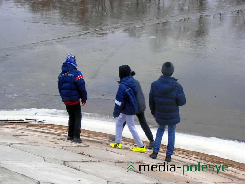 Вездесущие пацаны не рискуют выходить на прибрежный лёд и пробуют его крепость камнями