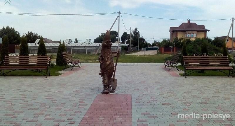 За памятником огурцу виднеются теплицы, в которых трудолюбивые полешуки выращивают огурцы