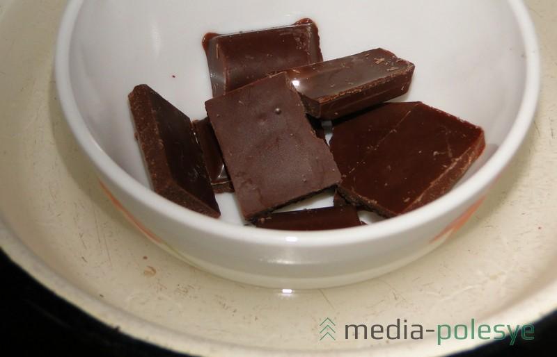 Налить в ёмкость крутого кипятка. Опустить туда мисочку с шоколадом (поломанным на дольки). Дать немного постоять, затем перемешать, чтобы не было комочков от ещё нераставшей плитки