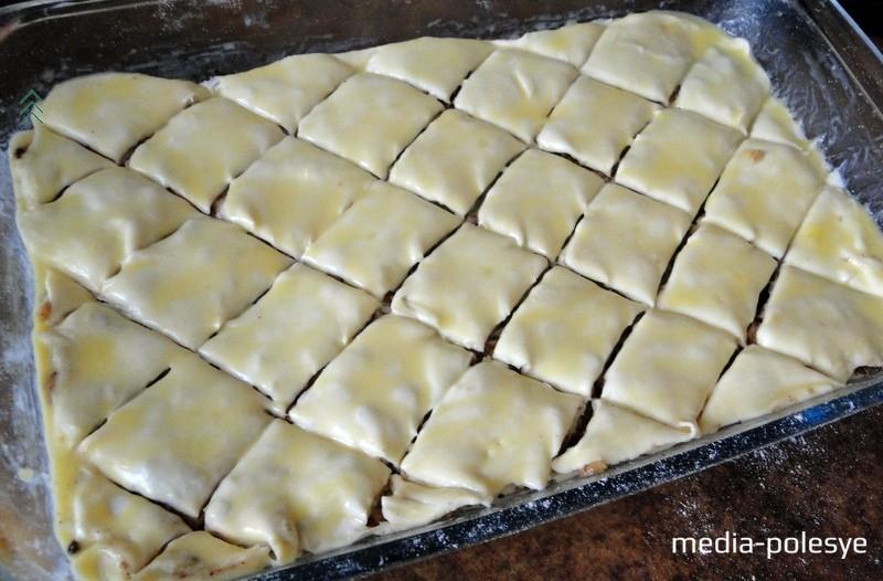 Накрываем следующим пластом теста. Продолжаем данные манипуляции, пока все слои теста и ореховой начинки не закончатся. Верхний слой должен быть из теста. Его смазываем желтком. Надрезаем пахлаву на небольшие ромбики и выпекаем в заранее разогрей до 180 градусов духовке 40–45 минут (до образования золотистой корочки). Можно в центр каждого ромбика положить по половинке грецкого ореха