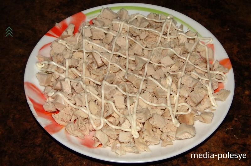 Приступаем к сборке салата. На сервировочное блюдо выкладываем первым слоем куриное филе. Поверх делаем решётку из майонеза