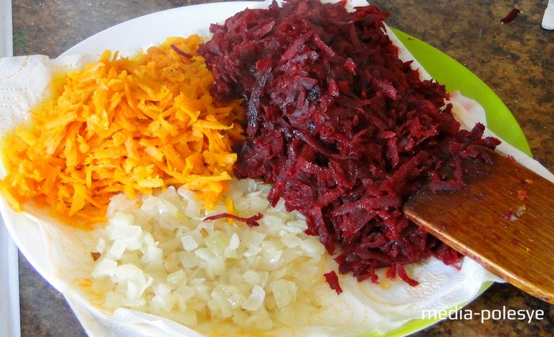 Лук, морковь и свеклу натереть на крупной тёрке и обжарить на растительном масле до готовности. Выложить на бумажное полотенце, чтобы оно впитало лишнее масло