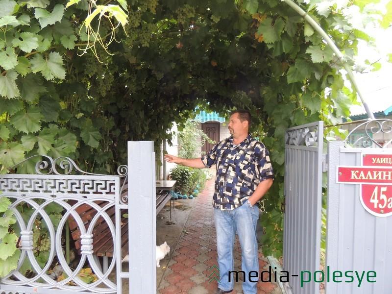 Николай Омельчук у арки из винограда около своего дома в Хорске
