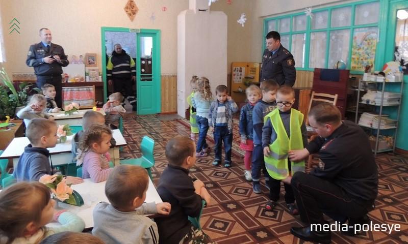 Станислав Соловей и Сергей Тропец объясняют детям порядок использования жилетов повышенной видимости