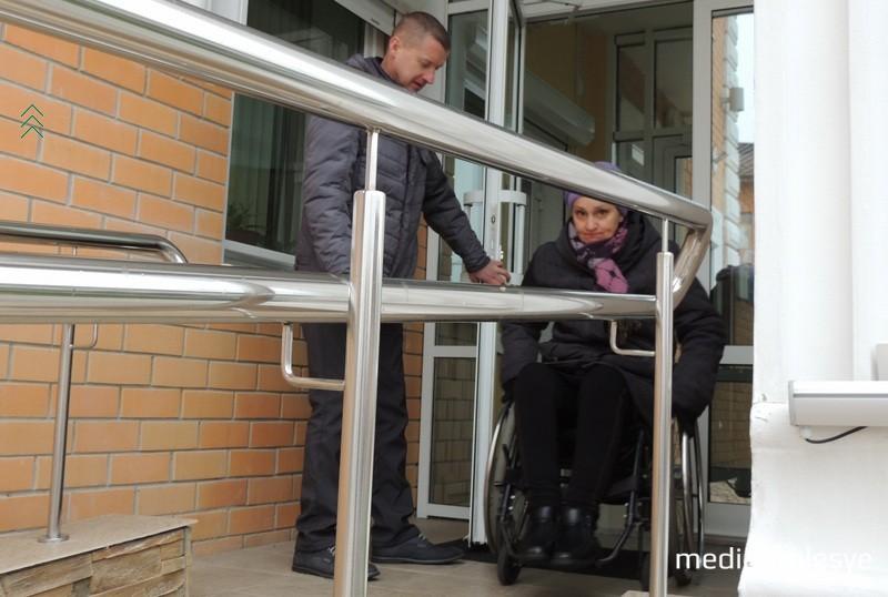 Если по пандусу Ольга поднялась самостоятельно, то дверь в здание открыть сама не смогла