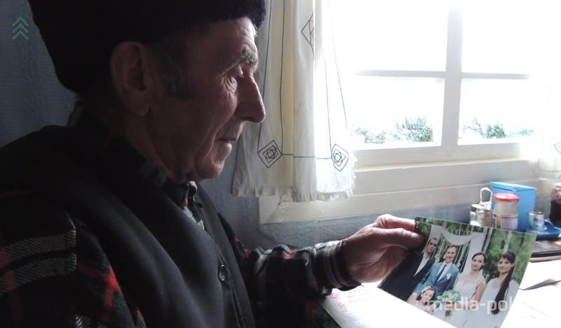 Віталь Сідаравіч разглядае вясельны фотаздымак унучкі Аліны