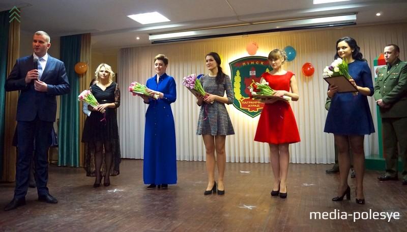 Начальник Пинского погранотряда Максим Бутранец поздравляет участниц и дарит им цветы и сертификаты на посещениеспа-салона