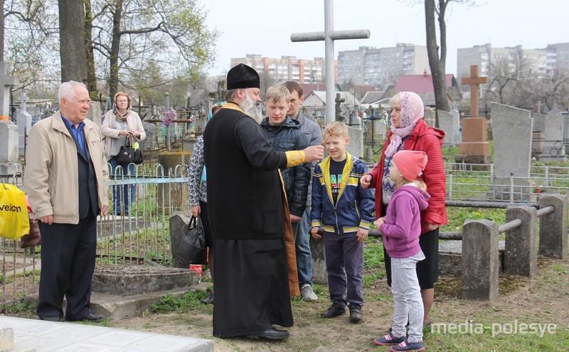 Священники поздравляют всех с Воскресением Христовым и идут освящать могилы
