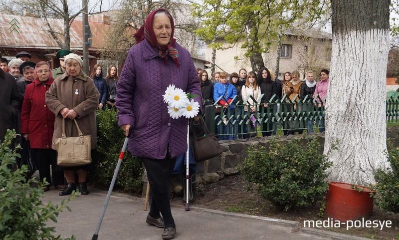 Бывшие узники несут цветы к памятному знаку