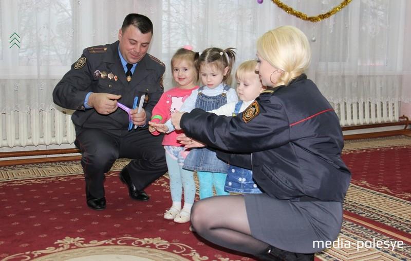 Яркие фликеры Сергей Тропец и Наталья Сахарчук надели деткам на руки. Фото ОГАИ Столинского РОВД