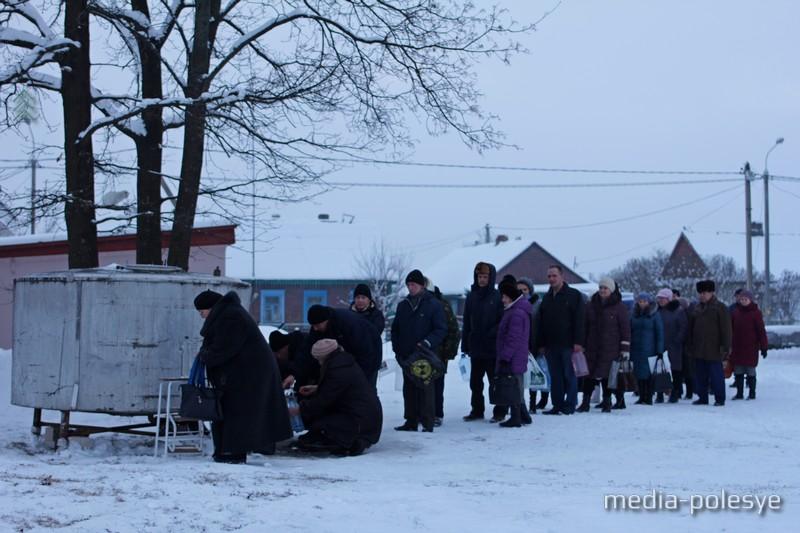 Прихожане Лунинецкого Свято-Крестовоздвиженского храма вечером 18 января набирают воду из установленного на территории храма чана
