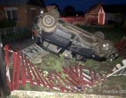 В Плотнице машина врезалась в забор, влетела во двор и опрокинулась