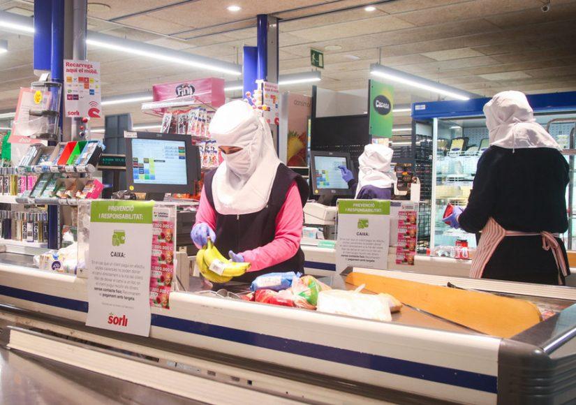 Продавцы в супермаркете Матаро, Каталония, работают в защитных костюмах. Фото Daniel Ferrer Paez, Shutterstock.com
