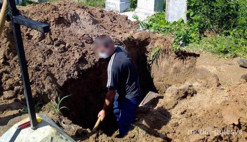 Работники ритуальной службы раскапывают могилу
