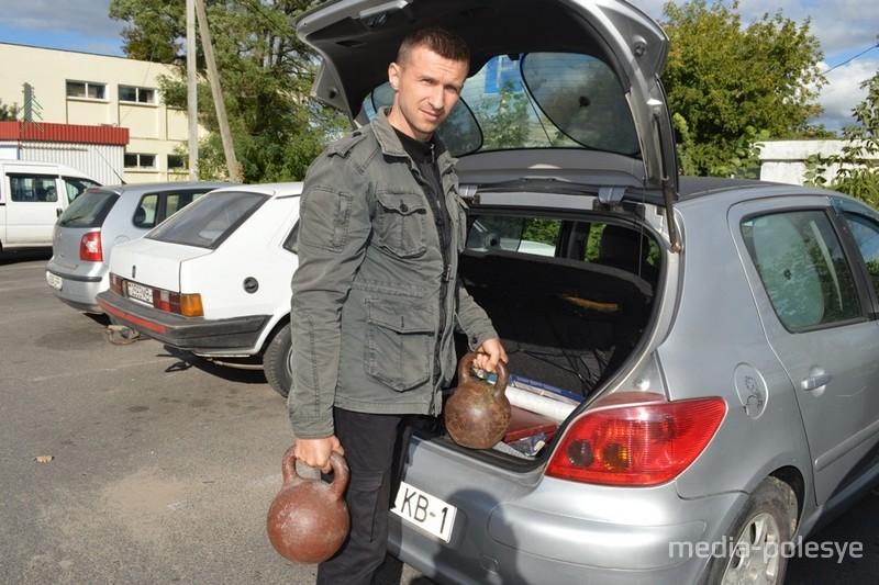 Игорь Киценко достаёт из багажника машины 36-килограммовые гири, которые всегда при нём