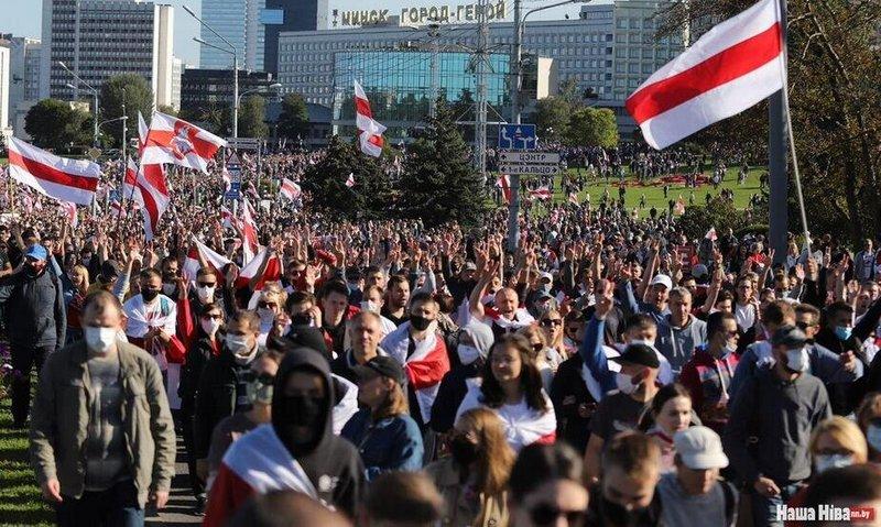 Демонстранты в Минске проходят под зданием с надписью «Минск — город-герой». Фото Надежды Бужан