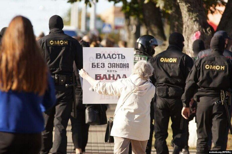 Пожилая женщина стыдит ОМОН в Гомеле плакатом «Власть без закона есть банда». Фото Svaboda.org