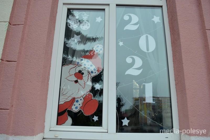 Бело-красно-белый дед Мороз выглядывает из окна учреждения, расположенного на центральной площади города