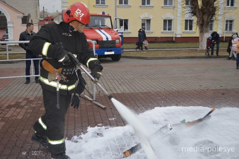 Спасатель-пожарный тушит то, что осталось от чучела