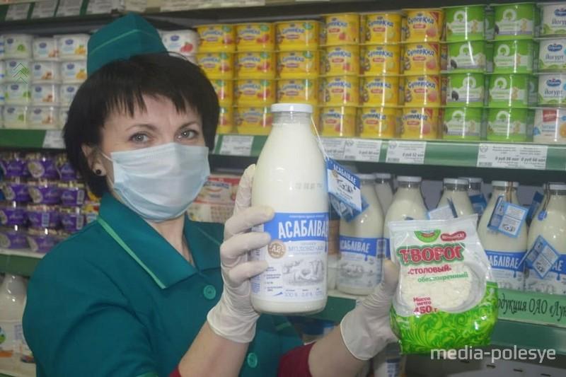 Продавец 5 разряда Ирина Харитонович демонстрирует молоко «Асаблiвае» и последнюю новинку завода – творог «Столовый»