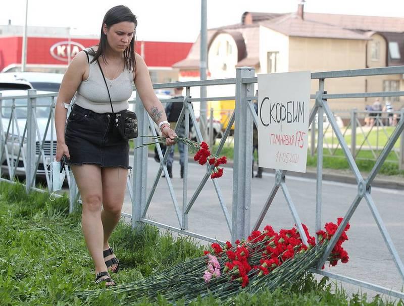 Местная жительница возлагает цветы у школы № 175, где появился стихийный мемориал / Фото: © Егор Алеев/ТАСС